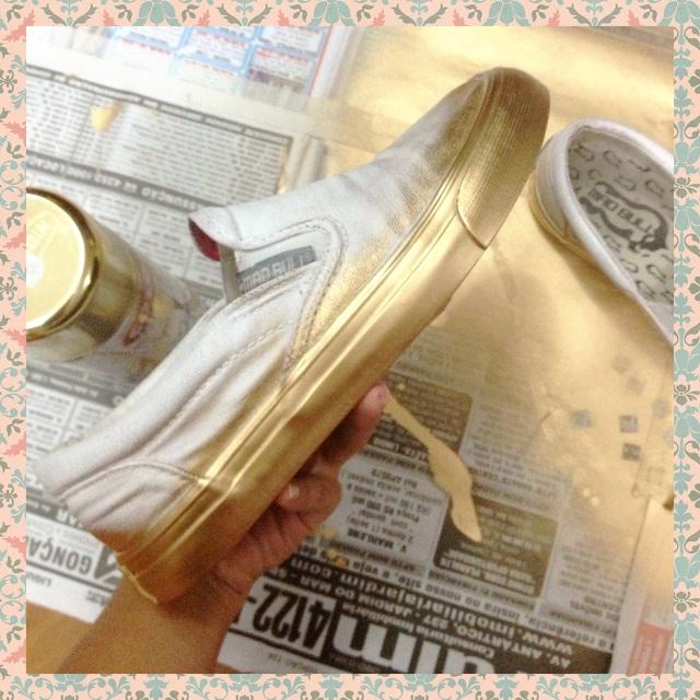 Com o spray dourado, pinte primeiramente a parte de corracha do tênis e depois de secar, pinte a parte do tecido